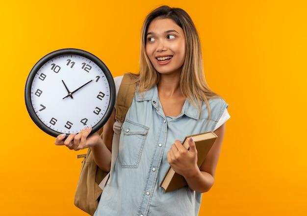 本と時計を保持し、オレンジ色に分離された側を見てバックバッグを身に着けているうれしそうな若いかわいい学生の女の子