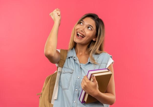 拳を上げてピンクで孤立して見上げる本を保持しているバックバッグを身に着けているうれしそうな若いかわいい学生の女の子