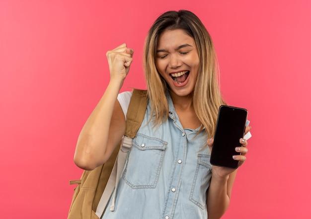 핑크에 고립 된 닫힌 된 눈으로 주먹을 올리는 휴대 전화를 들고 다시 가방을 입고 즐거운 젊은 예쁜 학생 소녀