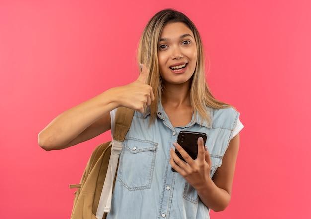 Gioiosa giovane ragazza graziosa dell'allievo che indossa la borsa posteriore che tiene il telefono cellulare e che mostra il pollice in su isolato sul colore rosa