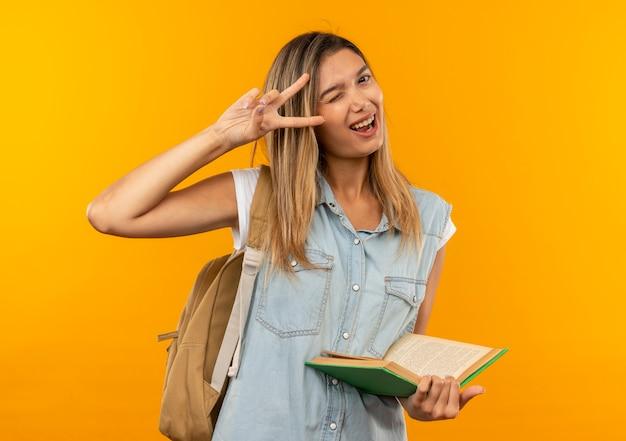Радостная молодая симпатичная студентка в задней сумке держит открытую книгу, подмигивая и делая знак мира, изолированного на оранжевом