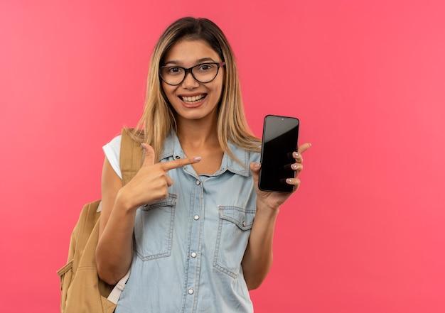 즐거운 젊은 예쁜 학생 소녀 안경을 쓰고 다시 가방을 들고 분홍색에 고립 된 휴대 전화를 가리키는