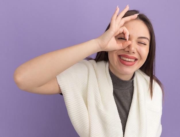 Gioiosa giovane donna graziosa che fa un gesto di sguardo guardando l'occhiolino anteriore isolato sul muro viola purple