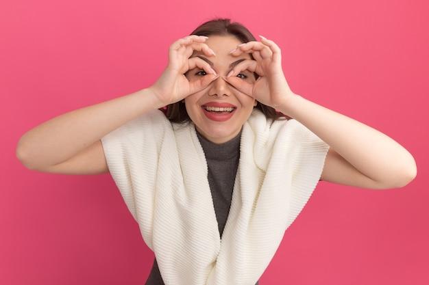 분홍색 벽에 격리된 쌍안경으로 손을 사용하여 표정 제스처를 하는 즐거운 젊은 예쁜 여성