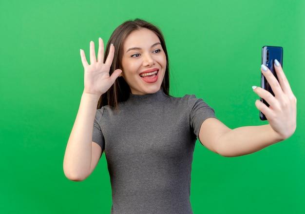 Радостная молодая красивая женщина, держащая глядя и размахивая мобильным телефоном, изолированным на зеленом фоне