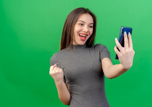 Gioiosa giovane donna graziosa che tiene e guardando il telefono cellulare e il pugno di serraggio isolato su sfondo verde con spazio di copia
