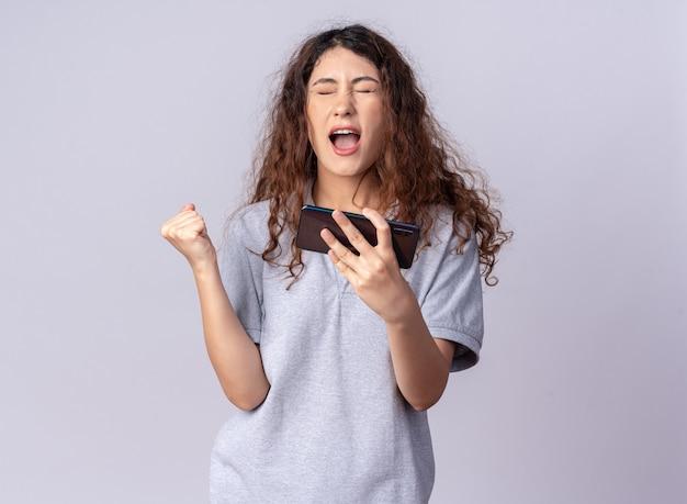 Gioiosa giovane donna graziosa che tiene il telefono cellulare facendo sì gesto con gli occhi chiusi isolati sul muro bianco con spazio copia