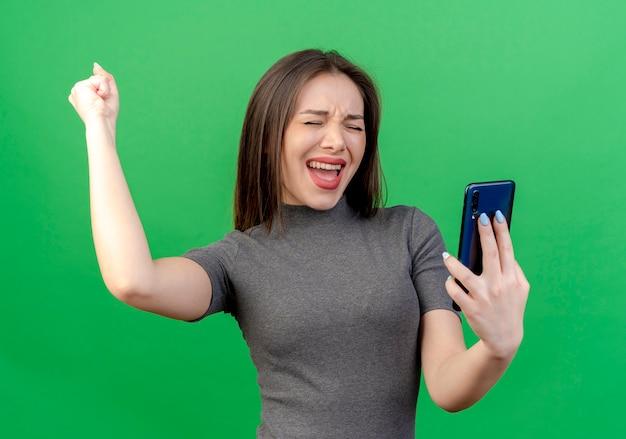 緑の背景に分離された目を閉じてイエスのジェスチャーを行う拳を上げる携帯電話を保持しているうれしそうな若いきれいな女性