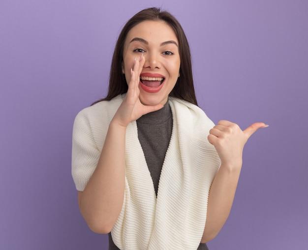 Gioiosa giovane donna graziosa che tiene la mano vicino alla bocca che punta al lato sussurrando isolata sul muro viola