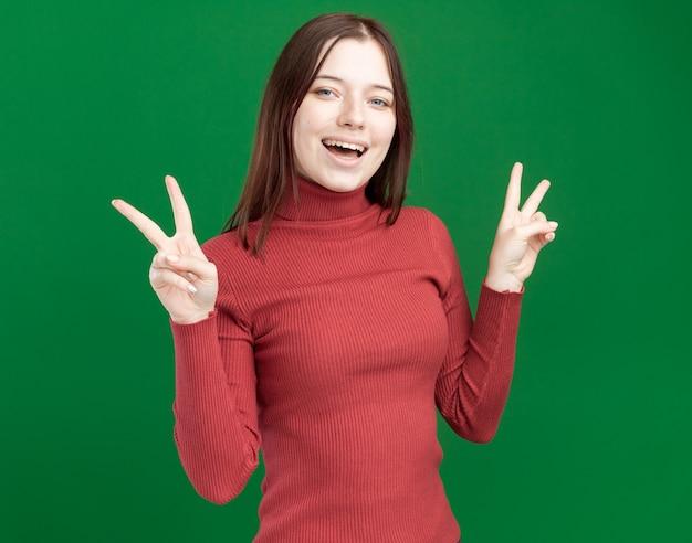 緑の壁に分離されたピースサインをやって正面を見てうれしそうな若いきれいな女性