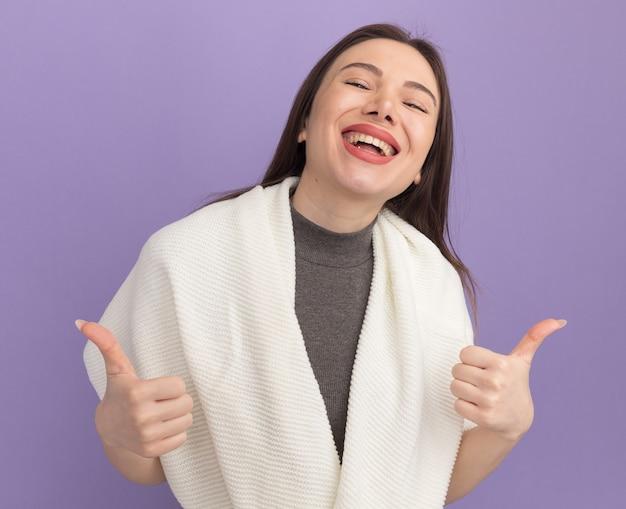 Gioiosa giovane bella donna che guarda davanti mostrando i pollici in su ridendo isolata sul muro viola