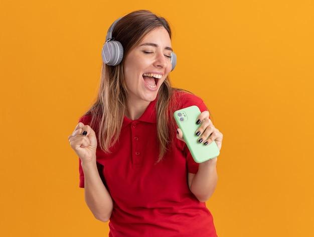 ヘッドフォンでうれしそうな若いきれいな女性は拳を保ち、オレンジ色の壁に隔離された電話を保持します