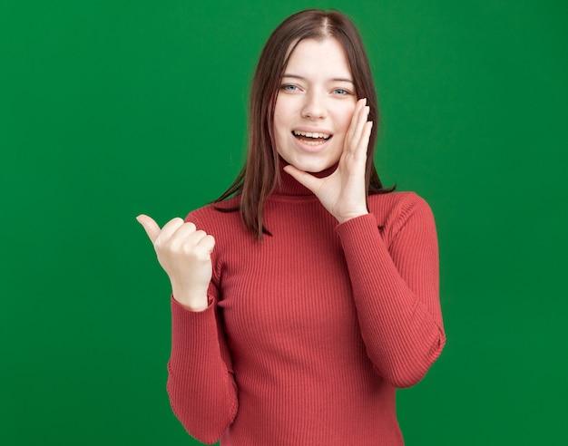 うれしそうな若いきれいな女性が口の近くでささやく手を保ちながら横を指しています