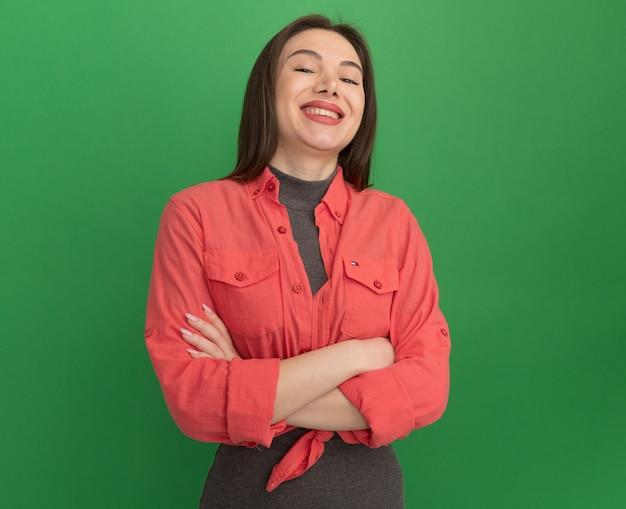 コピースペースと緑の壁に孤立して笑って閉じた姿勢で立っているうれしそうな若いきれいな女性