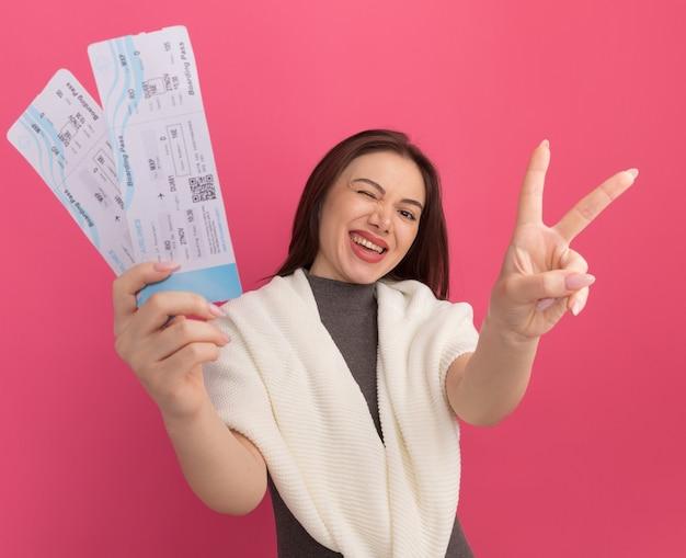 ピンクの壁に分離された平和のサインをやって飛行機のチケットを伸ばすうれしそうな若いきれいな女性 無料写真