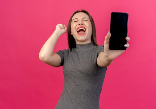 Gioiosa giovane donna graziosa che allunga il telefono cellulare alla telecamera alzando il pugno con gli occhi chiusi isolato su sfondo rosa con spazio di copia