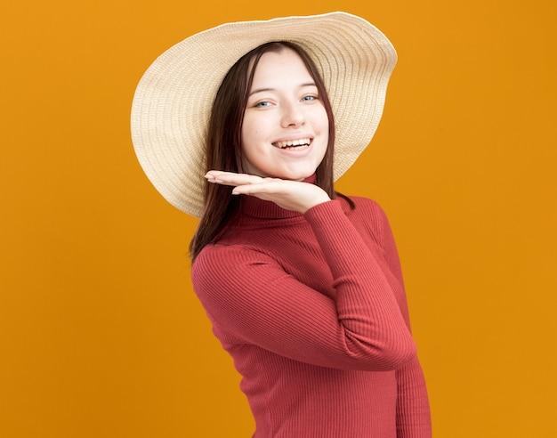 コピースペースでオレンジ色の壁に隔離されたあごの下で手を維持しながら正面を見て縦断ビューで立っているビーチ帽子をかぶってうれしそうな若いきれいな女性