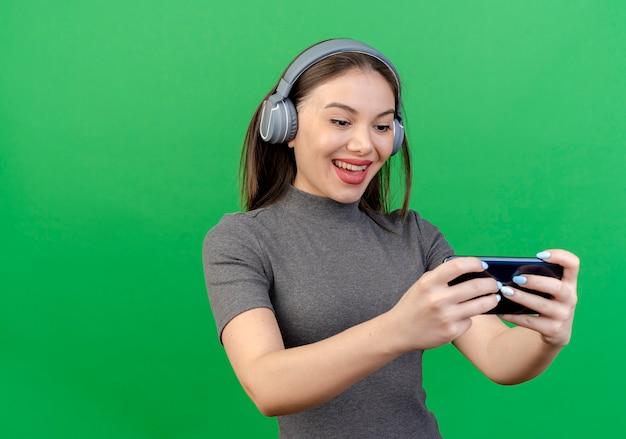 헤드폰을 착용하고 복사 공간이 녹색 배경에 고립 된 휴대 전화를 사용하는 즐거운 젊은 예쁜 여자