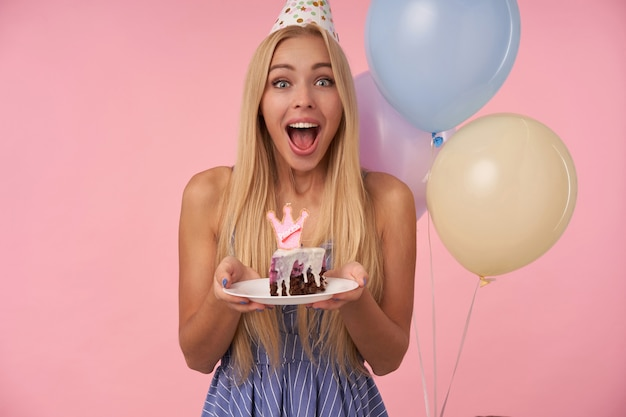 Gioiosa giovane donna graziosa con lunghi capelli biondi che indossa abiti estivi blu e cappello a cono, festeggia il compleanno e tiene un pezzo di torta in mano, sorridendo ampiamente su sfondo rosa