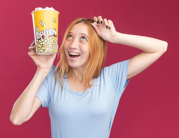 Gioiosa giovane ragazza rossa allo zenzero con le lentiggini che tiene in mano un secchio di popcorn e guarda in alto