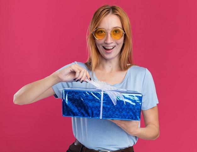Радостная молодая рыжая рыжая девушка с веснушками в солнцезащитных очках держит подарочную коробку