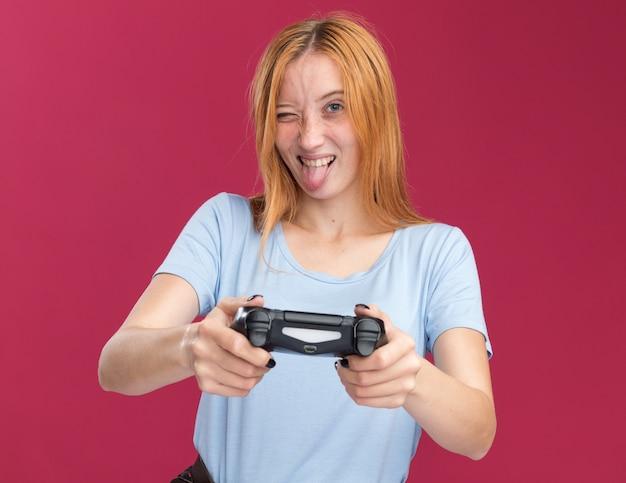 Радостная молодая рыжая рыжая девушка с веснушками высунула язык и держит игровой контроллер на розовом