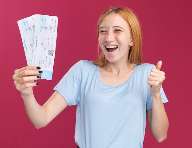 Gioiosa giovane ragazza rossa allo zenzero con le lentiggini che sfoglia e tiene in mano i biglietti aerei isolati sulla parete rosa con lo spazio della copia