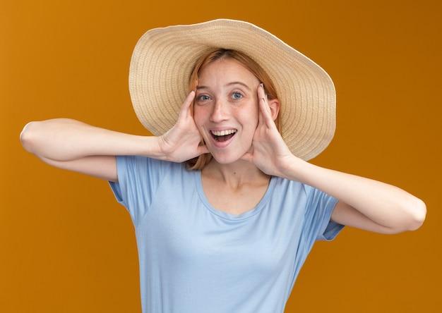ビーチ帽子をかぶってそばかすとうれしそうな若い赤毛の生姜の女の子は、コピースペースでオレンジ色の壁に隔離された顔に手を置きます