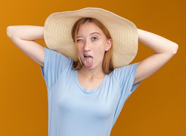 Радостная молодая рыжая рыжая девушка с веснушками в пляжной шляпе высовывает язык и кладет руки на голову сзади на оранжевом