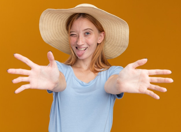Joyful young redhead ginger girl with freckles wearing beach hat stucks out tongue and blinks eye stretching out hands on orange