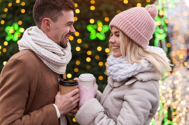 Joyful young romantic couple in warm winter clothes