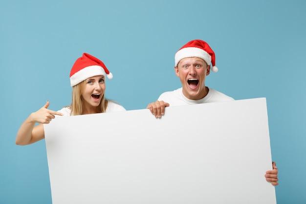 クリスマスの帽子のうれしそうな若いサンタカップルの友人の男と女