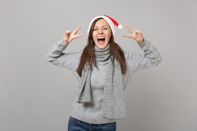スタジオの灰色の壁の背景に分離された勝利のサインを示す灰色のセータースカーフクリスマス帽子のうれしそうな若いサンタの女の子。明けましておめでとうございます2019お祝いホリデーパーティーのコンセプト。コピースペースをモックアップします。