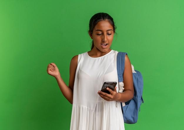 Gioiosa giovane studentessa indossando zaino tenendo e guardando il telefono e mostrando il gesto di sì