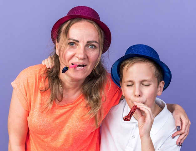 Joyful young slavic boy with blue party hat blowing party whistle with his mother wearing violet party hat isolated on purple wall with copy space