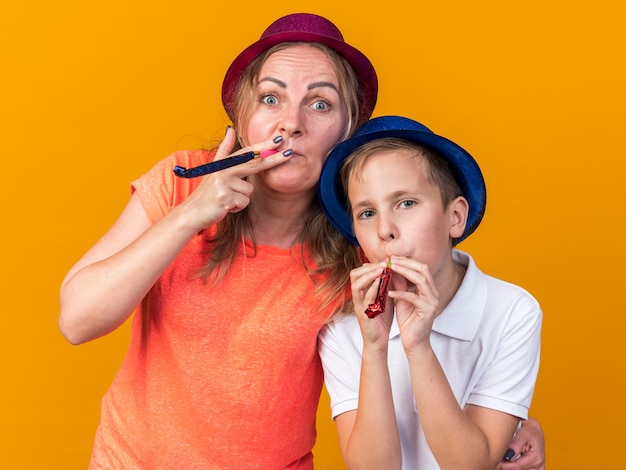 Joyful young slavic boy with blue party hat and his mother wearing violet party hat blowing party whistle isolated on orange wall with copy space