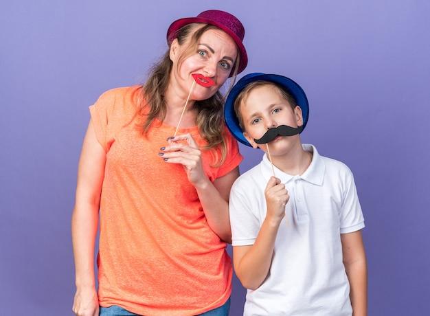 青いパーティーハットを持ったうれしそうな若いスラブ少年は、紫色のパーティーハットをかぶって、紫色の壁に偽の唇を持っている母親と一緒に立っている棒に偽の口ひげを持っています