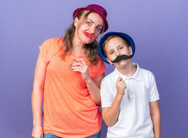Joyful young slavic boy with blue party hat holding fake mustache on stick standing with his mother wearing violet party hat and holding fake lips on stick on purple wall
