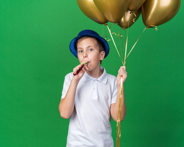 Joyful young slavic boy with blue party hat holding helium balloons and blowing party whistle isolated on green wall with copy space