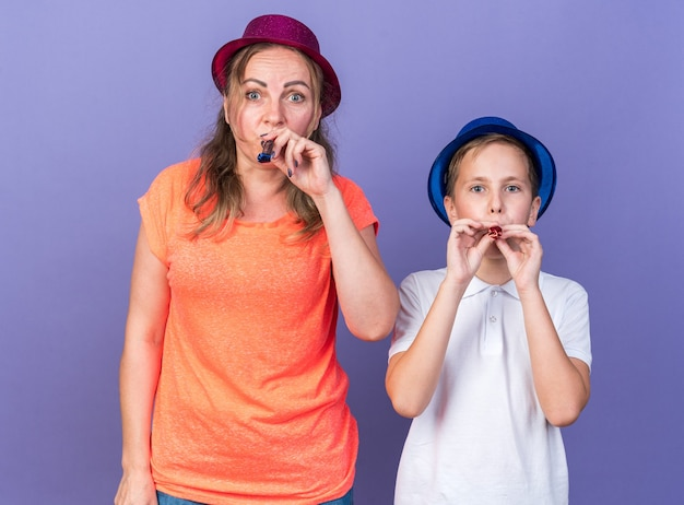 Joyful young slavic boy with blue party hat standing with his mother wearing violet party hat blowing party whistle isolated on purple wall with copy space