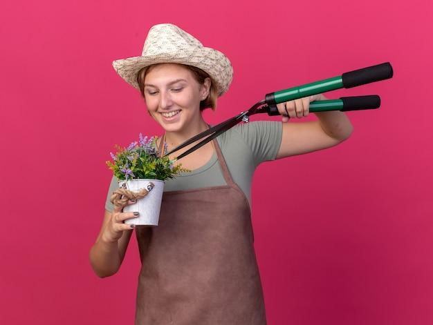 Gioiosa giovane giardiniere femmina slava che indossa cappello da giardinaggio tenendo forbici da giardinaggio e guardando i fiori in vaso di fiori isolato sulla parete rosa con spazio di copia