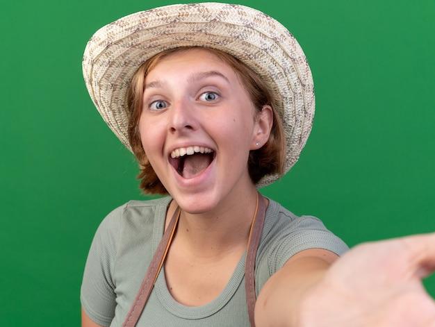 정원 가꾸기 모자를 쓴 즐거운 젊은 슬라브 여성 정원사는 복사 공간이 있는 녹색 벽에 격리된 셀카를 찍는 카메라를 들고 있는 척