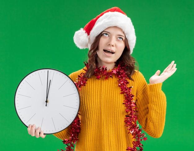 Радостная молодая славянская девушка в новогодней шапке и с гирляндой на шее держит часы и держит руку открытой, глядя вверх, изолированную на зеленом фоне с копией пространства