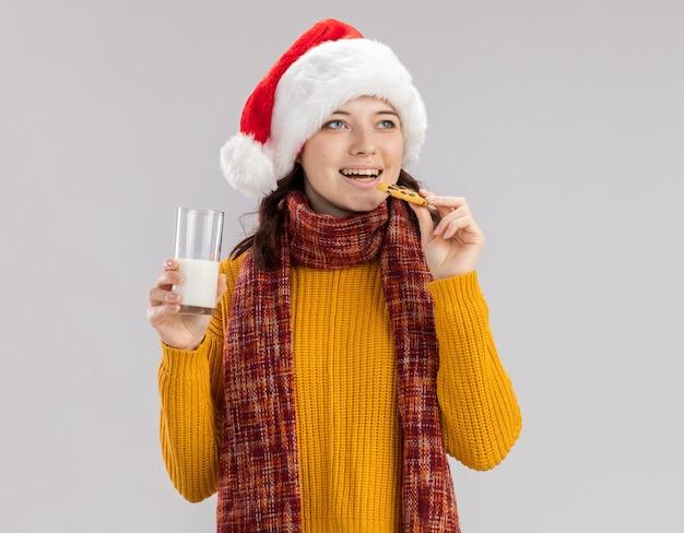 산타 모자와 목에 스카프와 우유와 비스킷의 유리를 들고 즐거운 젊은 슬라브 소녀 복사 공간이 흰 벽에 고립 된 측면을보고