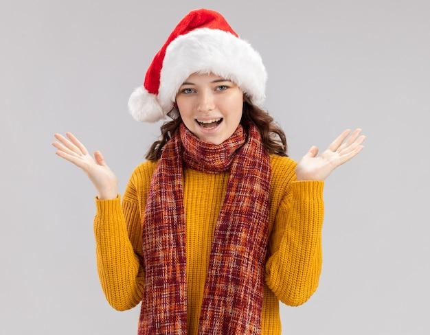 サンタの帽子と首の周りにスカーフを持って手を開いてコピースペースで白い背景で隔離のうれしそうな若いスラブの女の子