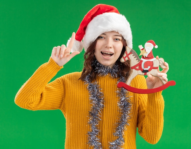 Joyful young slavic girl with santa hat and with garland around neck holding santa on rocking horse decoration and pointing up isolated on green background with copy space