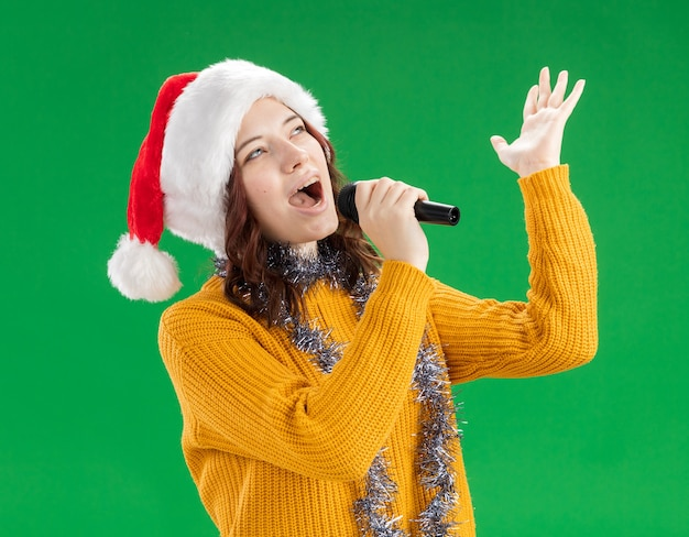 Joyful young slavic girl with santa hat and with garland around neck holds mic pretending to sing isolated on green wall with copy space