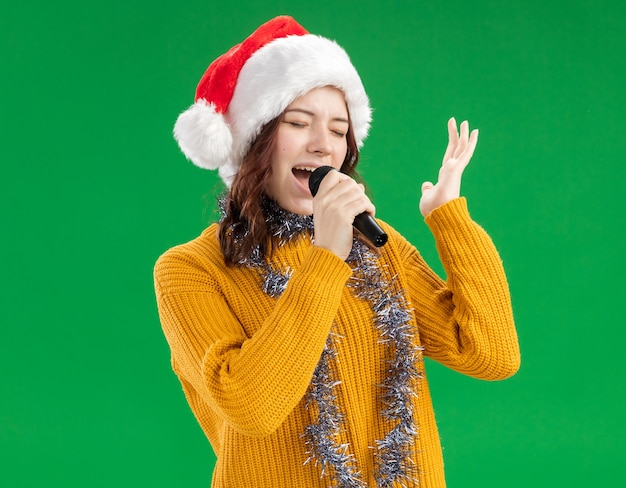 Joyful young slavic girl with santa hat and with garland around neck holds mic pretending to sing with closed eyes
