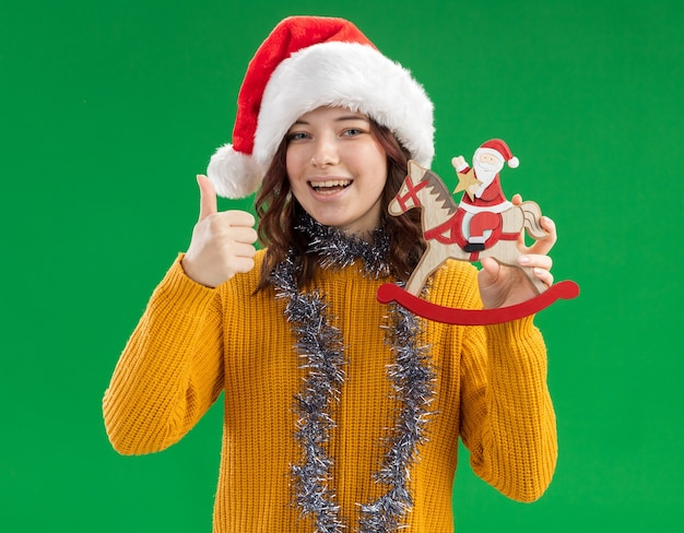 Joyful young slavic girl with santa hat and with garland around neck holds santa on rocking horse decoration and thumbs up