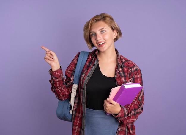 배낭을 입고 즐거운 젊은 슬라브 학생 소녀 옆에 책과 노트북 포인트를 보유